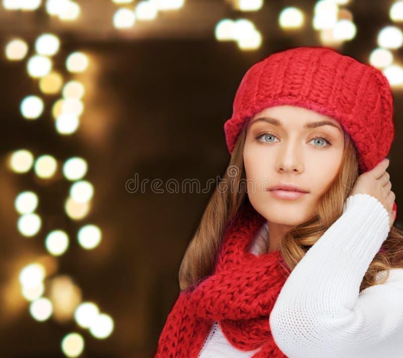 Mujer en sombrero y bufanda sobre fondo de las luces fotografía de archivo