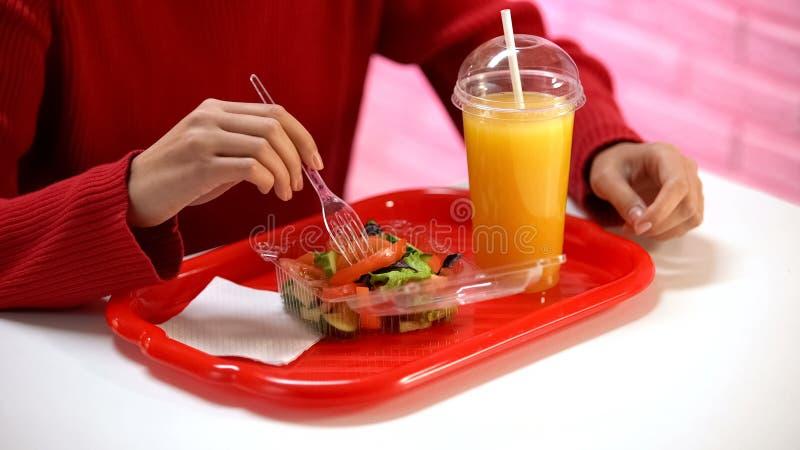 Mujer en su?ter rojo que come la ensalada vegetal en la cafeter?a, zumo de naranja en la tabla foto de archivo libre de regalías