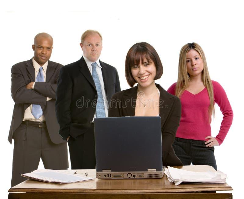 Mujer en su escritorio con los colegas foto de archivo libre de regalías