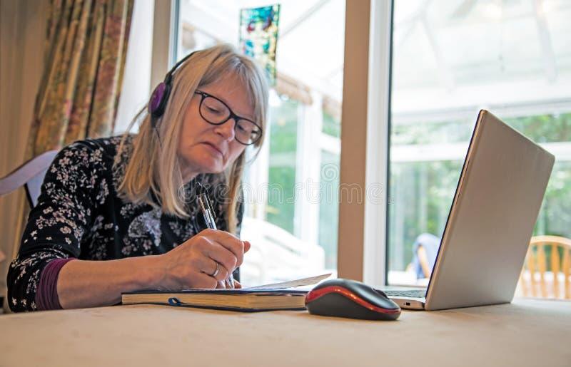 Mujer en su ordenador portátil que escucha auriculares webinar, que llevan imagenes de archivo