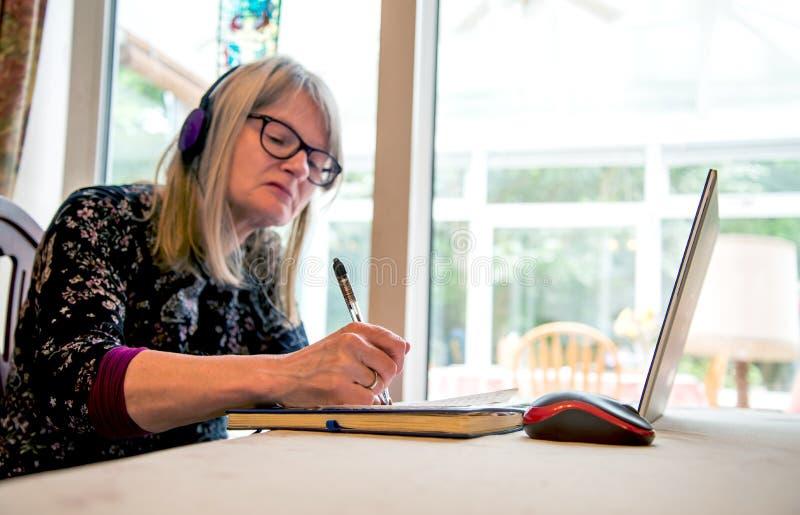 Mujer en su ordenador portátil que mira auriculares webinar, que llevan fotografía de archivo