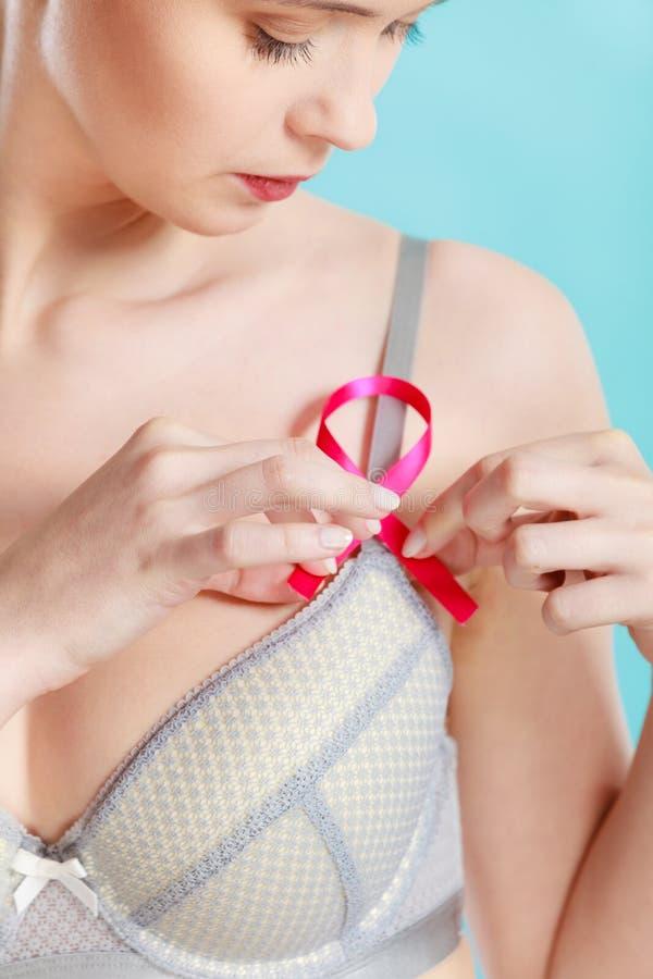 Mujer en sujetador con la cinta de la conciencia del cáncer de pecho imagen de archivo libre de regalías