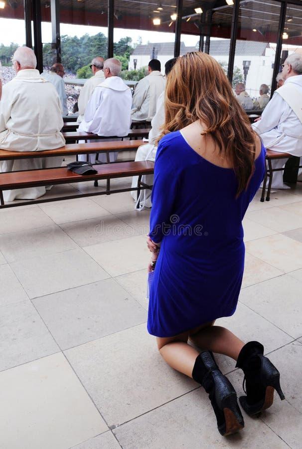 Mujer en sus rodillas en rezo, Christian Priests, fe foto de archivo