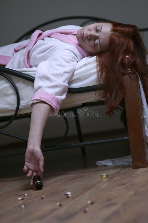 Mujer en tablilla de la sobredosis de la cama fotografía de archivo libre de regalías