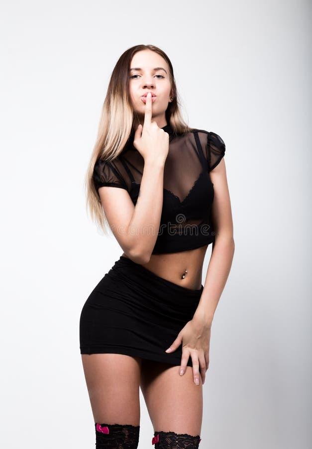 Mujer en tacones altos, tiro de la moda de los jóvenes del estudio la mujer en una falda negra corta y un top transparente puso s foto de archivo libre de regalías
