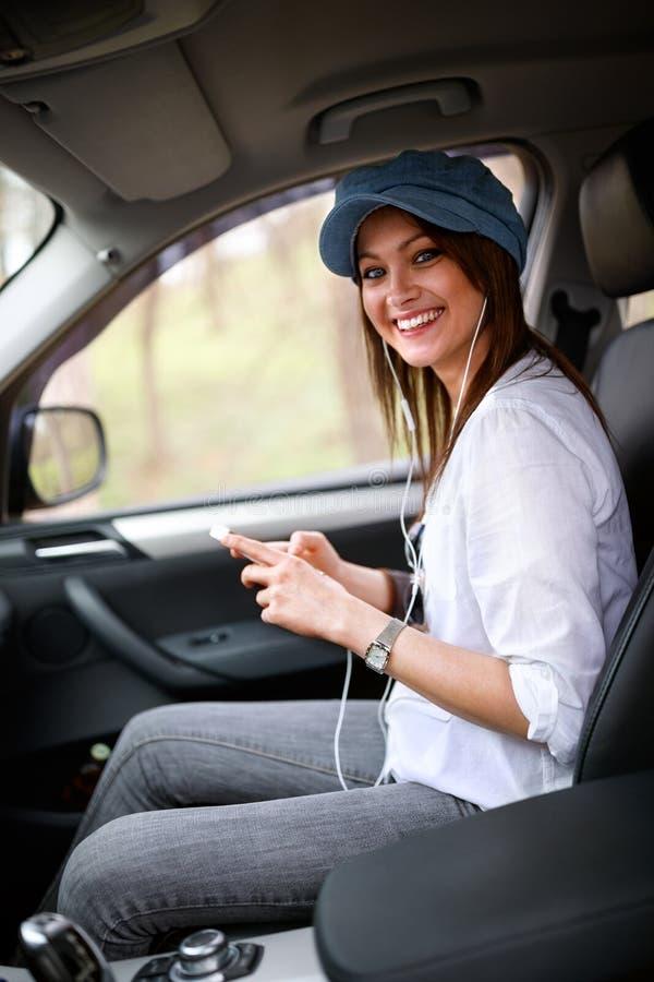 Mujer en teléfono celular de tenencia del coche fotos de archivo