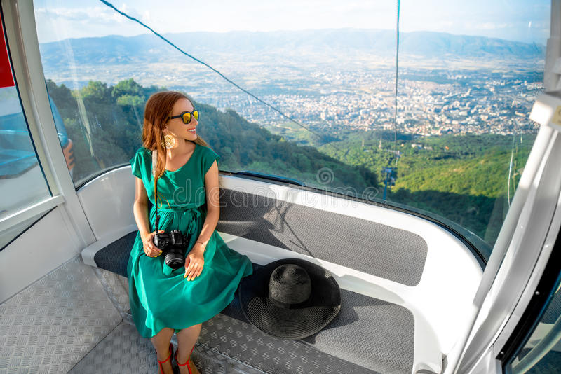 Mujer en teleférico con la opinión del paisaje urbano foto de archivo
