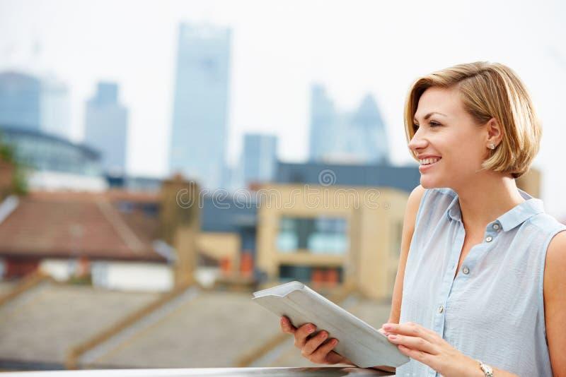 Mujer en terraza del tejado usando la tableta de Digitaces fotos de archivo