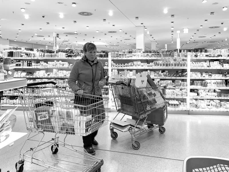 Mujer en tienda alemana cerca del carro de la compra fotografía de archivo