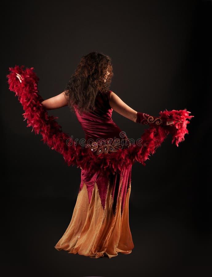 Mujer en traje árabe rojo oscuro con la boa fotografía de archivo libre de regalías