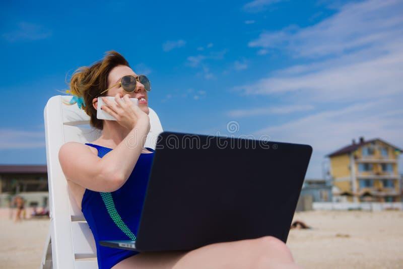 Mujer en traje de baño con el teléfono y el ordenador portátil imagen de archivo libre de regalías