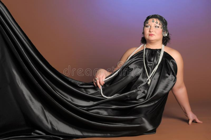 Mujer en trajes orientales en negro con las perlas foto de archivo
