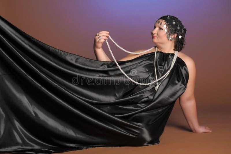 Mujer en trajes orientales en negro con las perlas fotografía de archivo