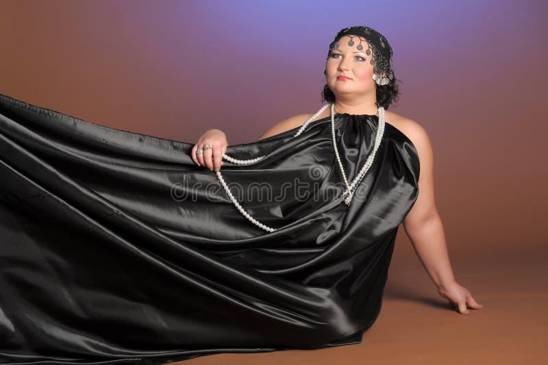 Mujer en trajes orientales en negro con las perlas imagenes de archivo
