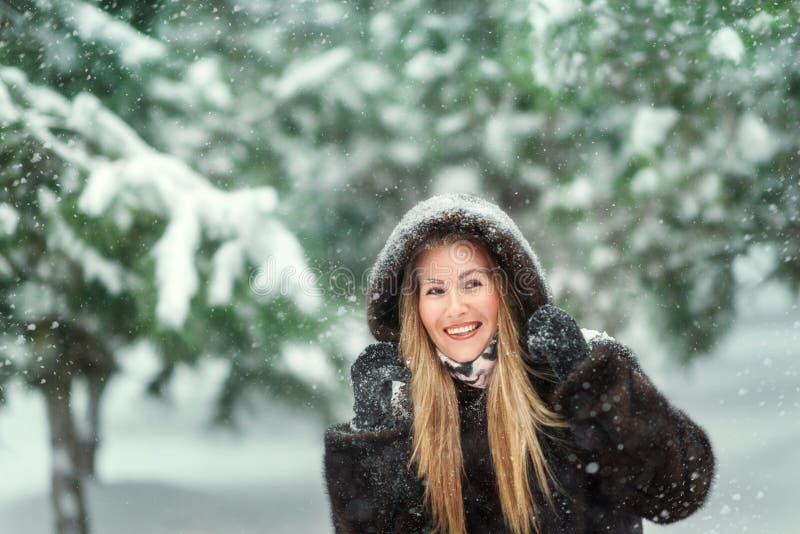 Mujer en un abrigo de pieles en bosque nevoso fotos de archivo