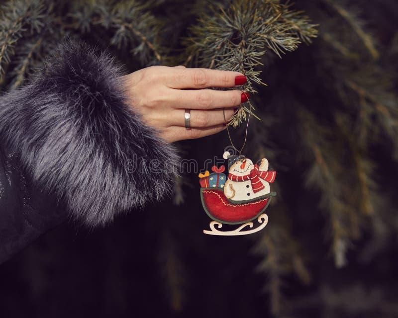 Mujer en un abrigo de pieles que adorna un árbol de navidad foto de archivo libre de regalías