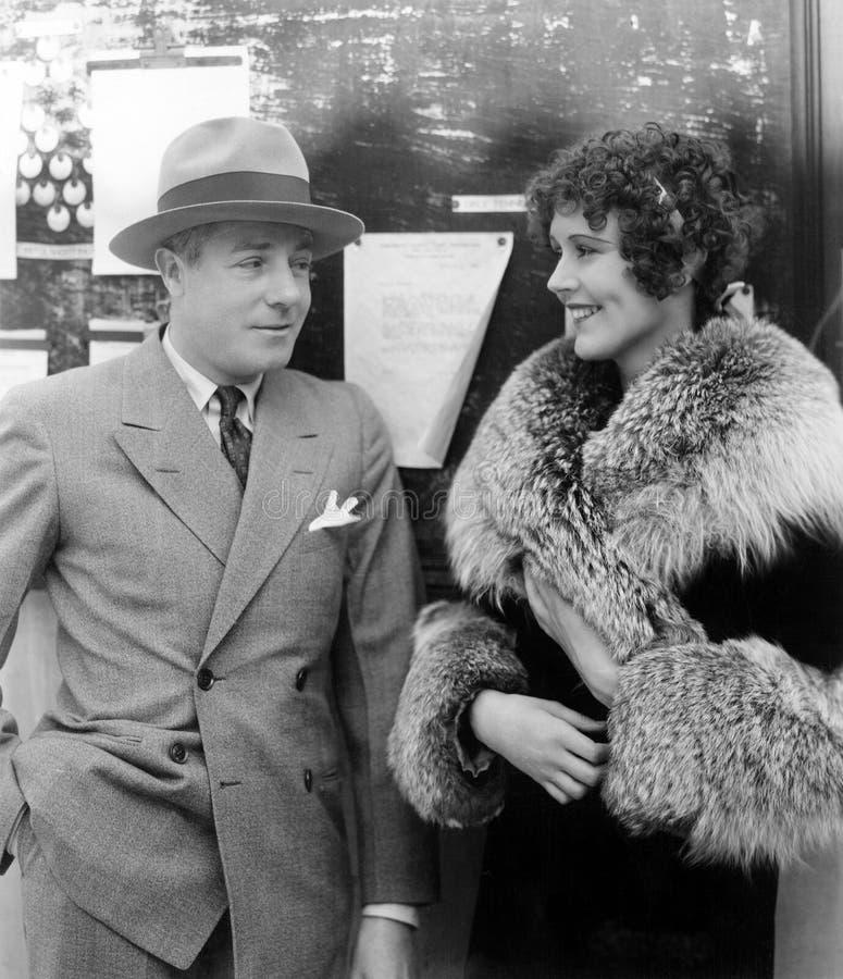 Mujer en un abrigo de pieles que tiene una conversación con un hombre (todas las personas representadas no son vivas más largo y  fotografía de archivo