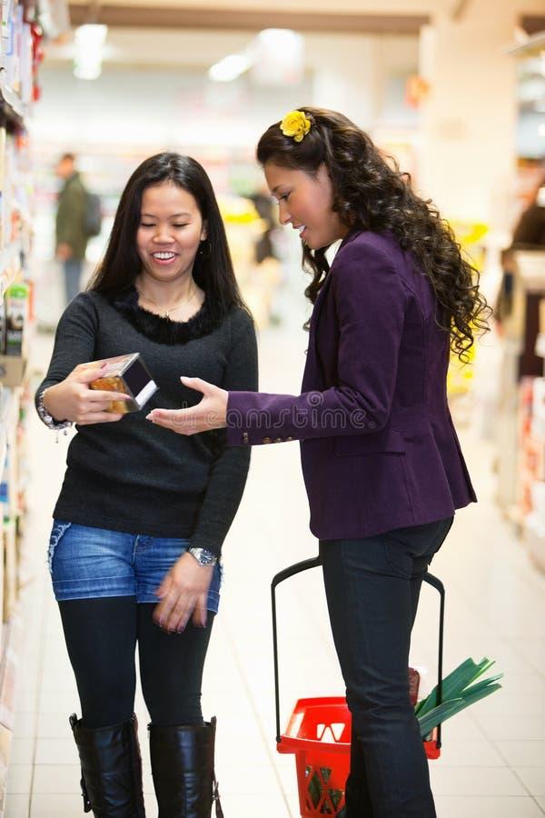Mujer en un almacén que mira un producto imagen de archivo