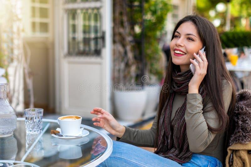 Mujer en un café y charlas en el teléfono móvil imagen de archivo libre de regalías