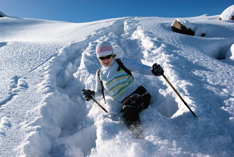 Mujer en un camino de la nieve en montañas imagen de archivo libre de regalías