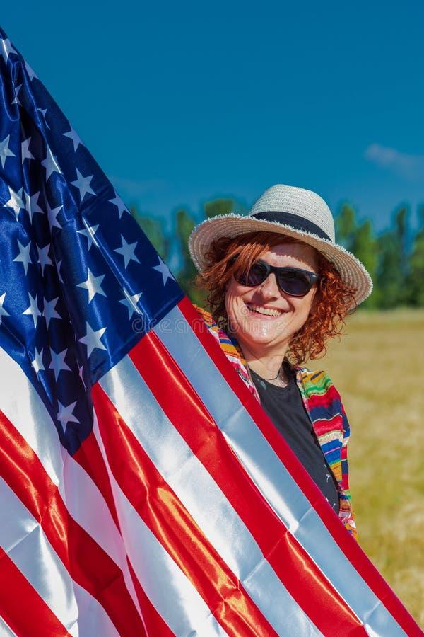 Mujer en un campo de trigo con una bandera de los E.E.U.U. imagen de archivo libre de regalías