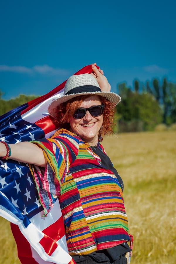 Mujer en un campo de trigo con una bandera de los E.E.U.U. imágenes de archivo libres de regalías