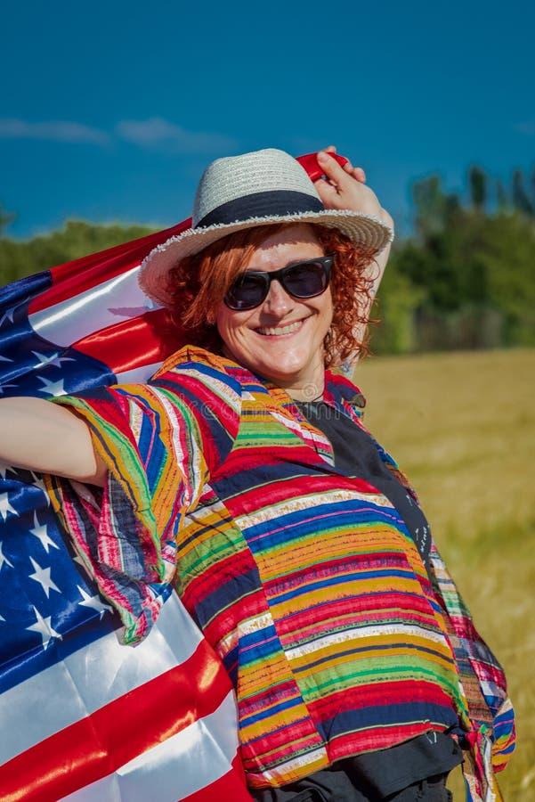 Mujer en un campo de trigo con una bandera de los E.E.U.U. imagenes de archivo