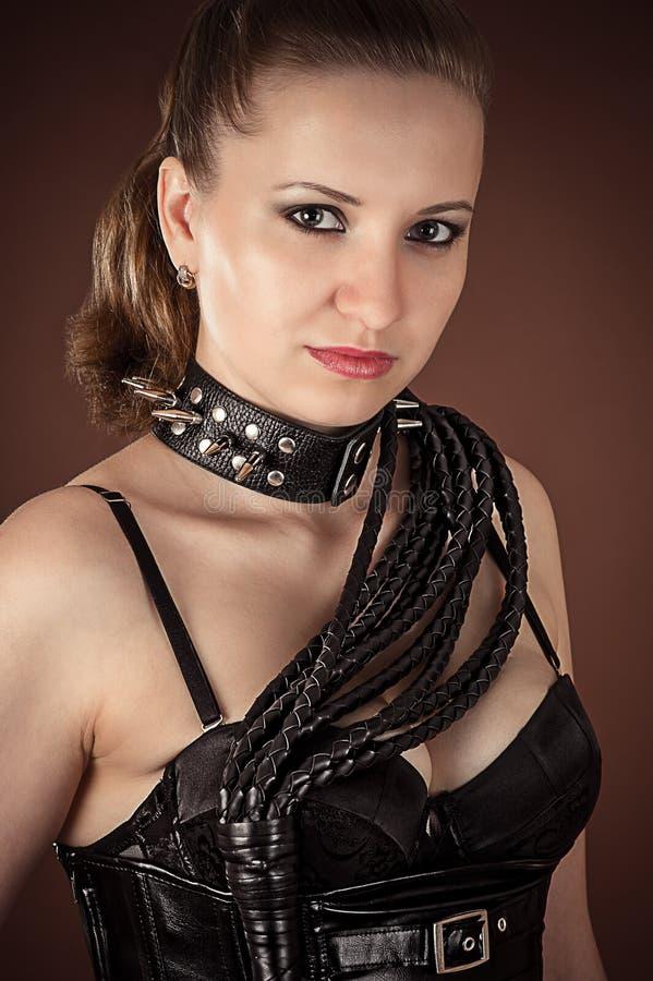 Mujer en un cuello claveteado con el azote imagen de archivo