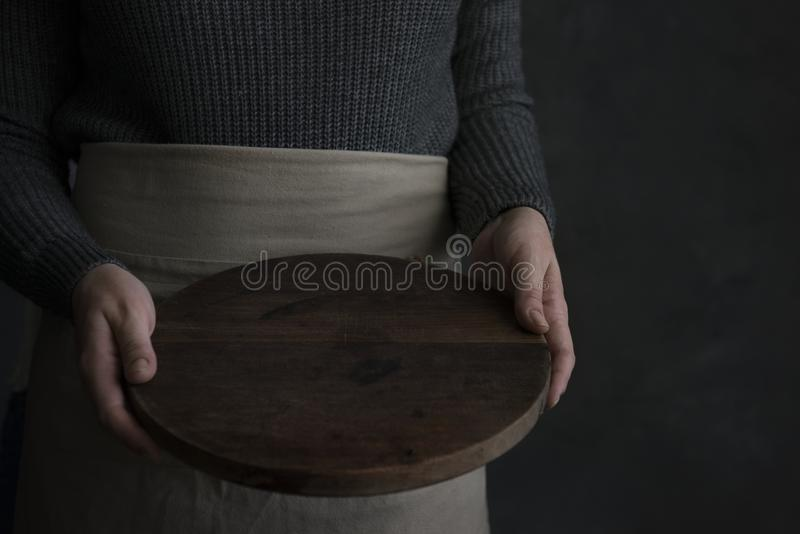 Mujer en un delantal que sostiene una bandeja de madera foto de archivo libre de regalías