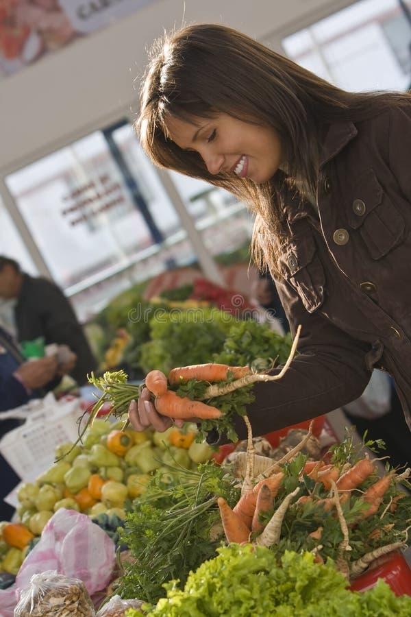 Mujer en un mercado vegetal. fotos de archivo