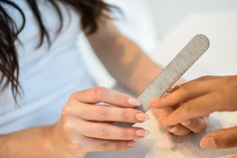 Mujer en un sal?n de los clavos que recibe una manicura con el fichero de clavo imagenes de archivo