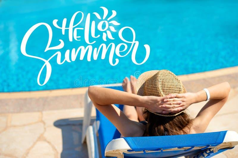 Mujer en un sombrero de paja que se relaja en una cubierta-silla cerca de una piscina azul lujosa y las letras hola verano, tiemp foto de archivo