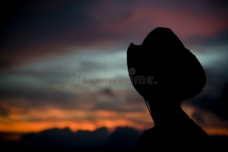 Mujer en un sombrero de vaquero silueteado contra una puesta del sol fotos de archivo libres de regalías