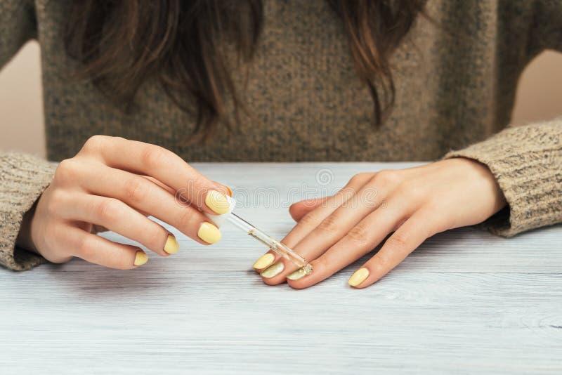 Mujer en un suéter marrón con la manicura amarilla que aplica el cosmético foto de archivo libre de regalías