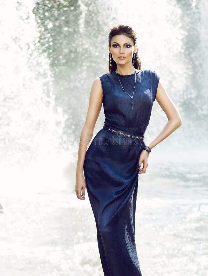 Mujer en un vestido azul cerca de una cascada foto de archivo