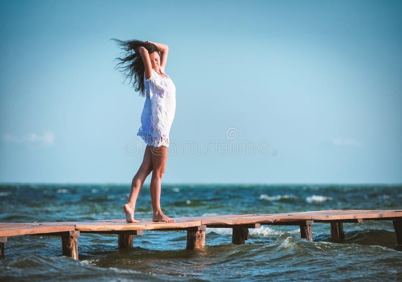 Mujer en un vestido blanco en la playa foto de archivo libre de regalías