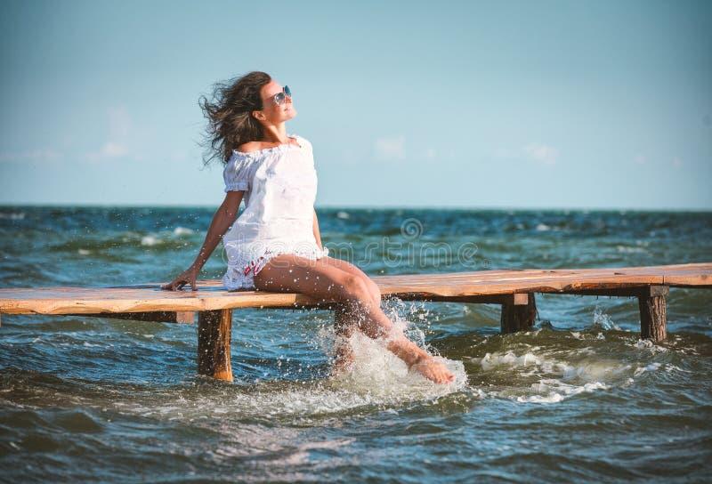 Mujer en un vestido blanco en la playa fotos de archivo