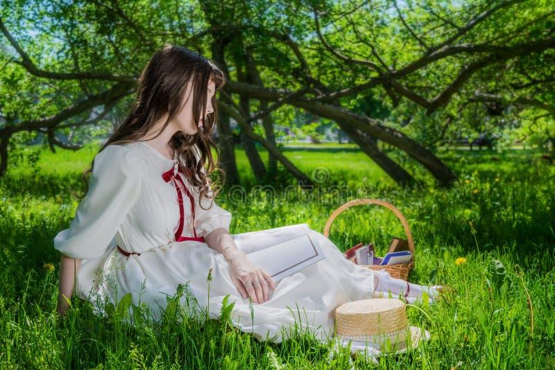 Mujer en un vestido blanco que se sienta debajo de lilas de un árbol foto de archivo libre de regalías