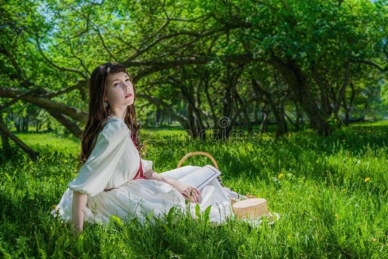 Mujer en un vestido blanco que se sienta debajo de lilas de un ?rbol imagenes de archivo