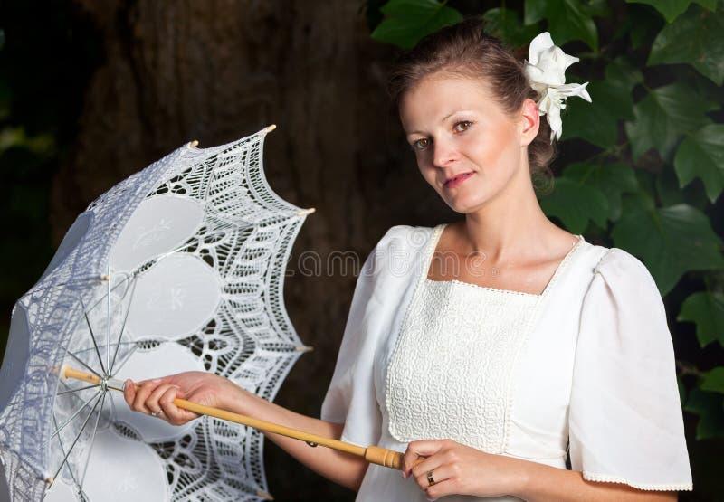 Mujer en un vestido blanco y con un paraguas del cordón imágenes de archivo libres de regalías