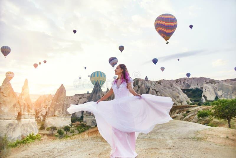 Mujer en un vestido largo en el fondo de globos en Cappadocia La muchacha con las manos de las flores se coloca en una colina y m imagen de archivo