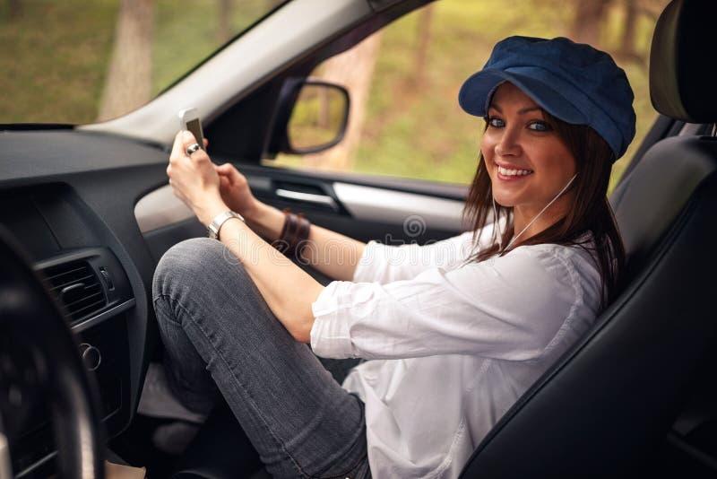 Mujer en un viaje por carretera Muchacha sonriente que escucha la música en su SM imagen de archivo