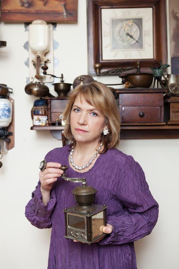 Mujer en una blusa púrpura con una amoladora de café vieja en sus manos imágenes de archivo libres de regalías