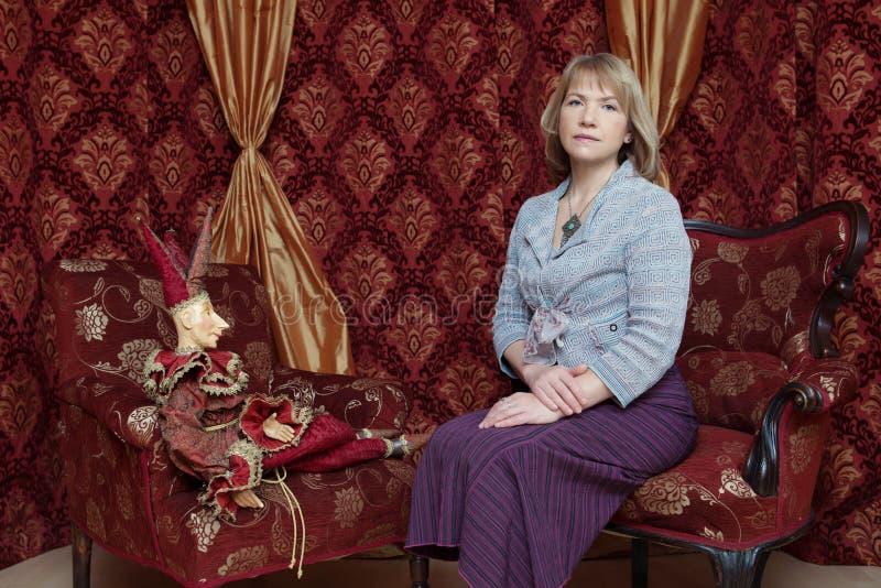 Mujer en una blusa púrpura con una amoladora de café vieja en sus manos fotografía de archivo libre de regalías