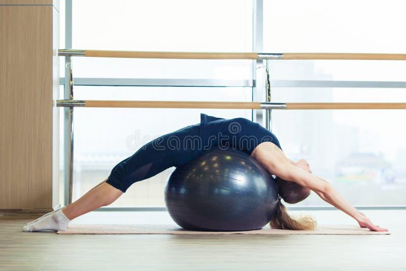 Mujer en una bola de la aptitud en gimnasio imagenes de archivo