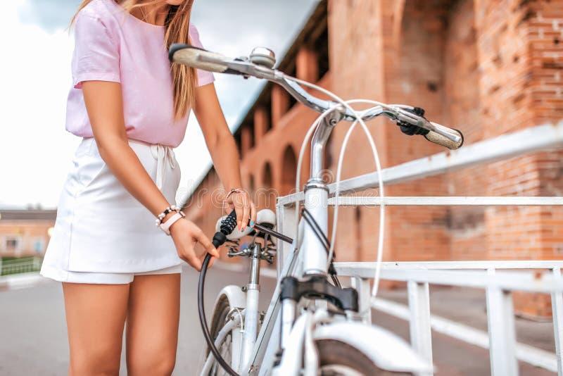 Mujer en una camiseta rosada cerca del aparcamiento de la cerca en el verano en el parque Cerraduras, cerraduras el cable con un  foto de archivo libre de regalías