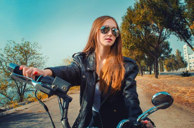 Mujer en una chaqueta de cuero y tejanos en vidrios en un mot foto de archivo
