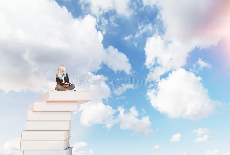 Mujer en una pila de libros imagen de archivo libre de regalías
