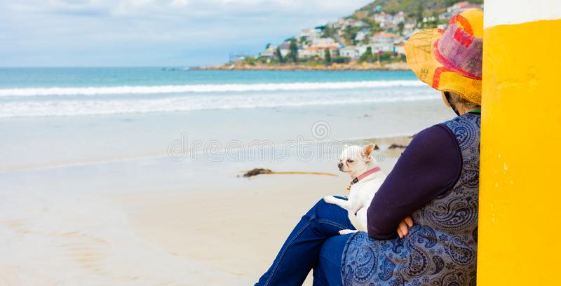 Mujer en una playa con un perro en su revestimiento fotografía de archivo