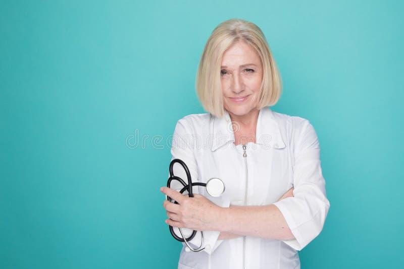 Mujer en una situación médica blanca de la ropa aislada en un fondo azul y que sostiene el estetoscopio en su mano imagenes de archivo